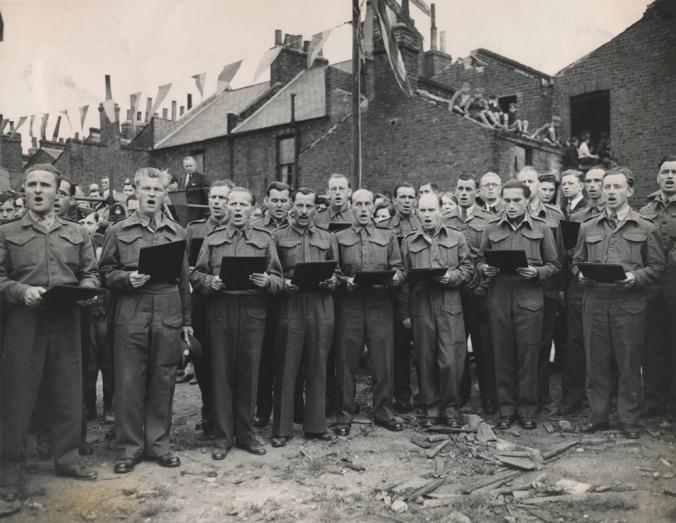 Czechoslovak servicemen in uniform from sing at Bermondsey Bomb site. Children sit watching from nearby roof.