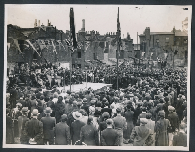 Memorial Service for Lidice at Spa Road bomb site on 10 June 1943. Crowd of people stand around a raised stage surrouned by flags and bunting against the backdrop of bomb damaged houses