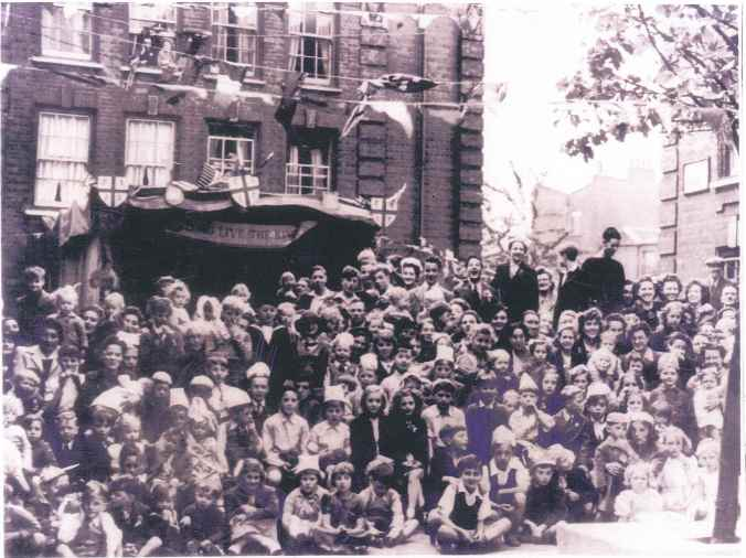 Victory Party 1945 (C Block Plough Way estate) - Aunt and Uncle in window, Ted one of kids below